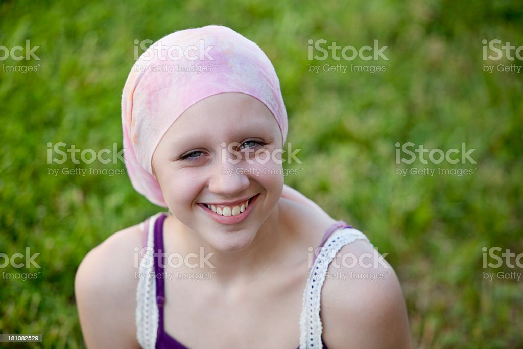 A happy young girl, who has cancer, wearing a head scarf stock photo