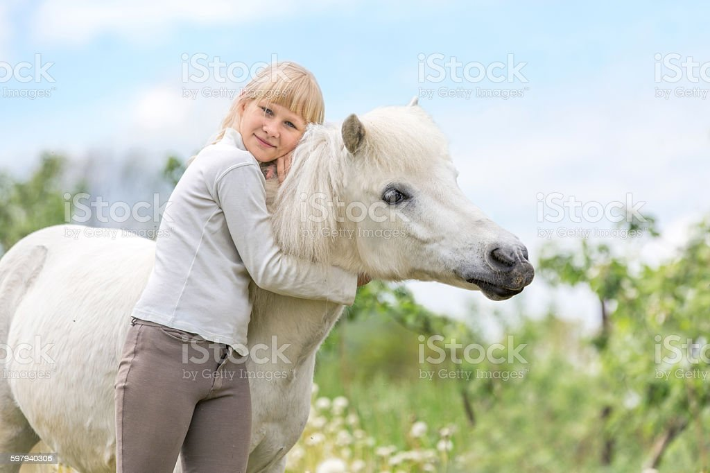 Happy young girl with a white shetland pony. foto royalty-free