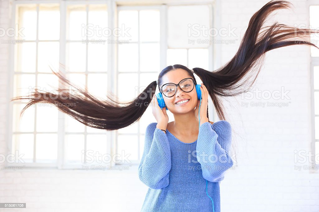 Happy young girl with blue headphones jumping stock photo