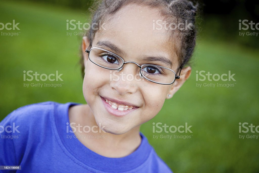 Happy Young Girl with Glasses Smiling Outside stock photo