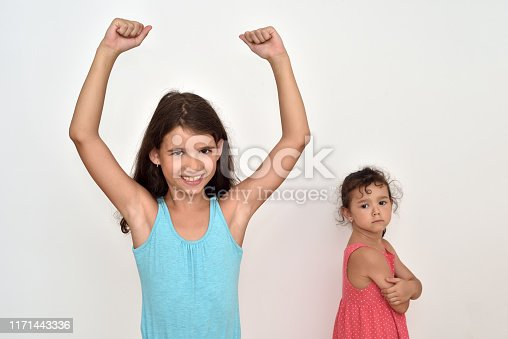 Happy and smiling cute young girl with hands up and her jealous and angry younger sister. Focus on the girl on the left.