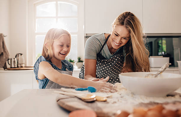 happy young girl with her mother making dough - een taart bakken stockfoto's en -beelden