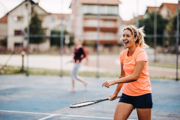 chicas joven felizes jugando al tenis - tenis fotografías e imágenes de stock