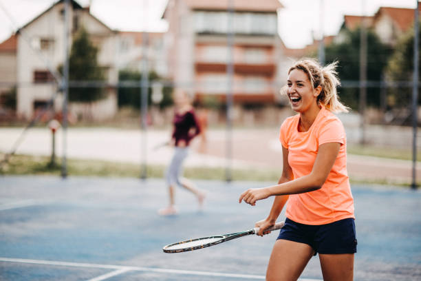 happy young girls playing tennis - tennis stock pictures, royalty-free photos & images