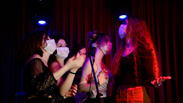 Happy young girls singing karaoke together in night club with protective face mask stock photo
