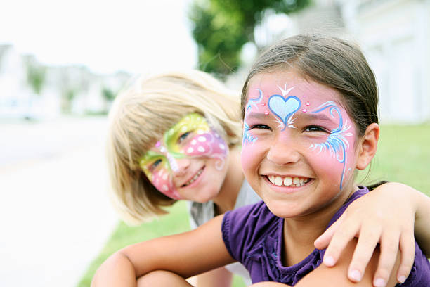 Happy young girls with painted faces stock photo