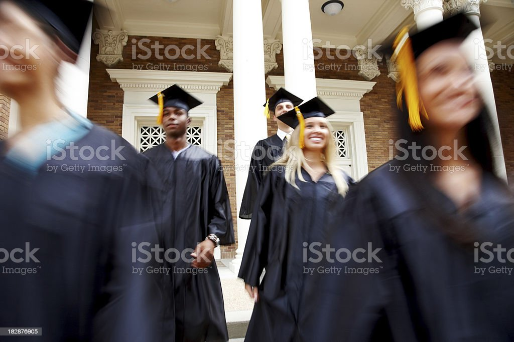 Happy young graduates standing in a line royalty-free stock photo