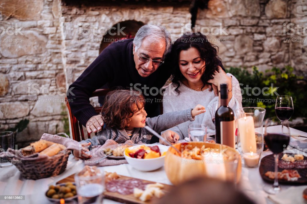 Happy young grandson having lunch at grandparents rustic house stock photo