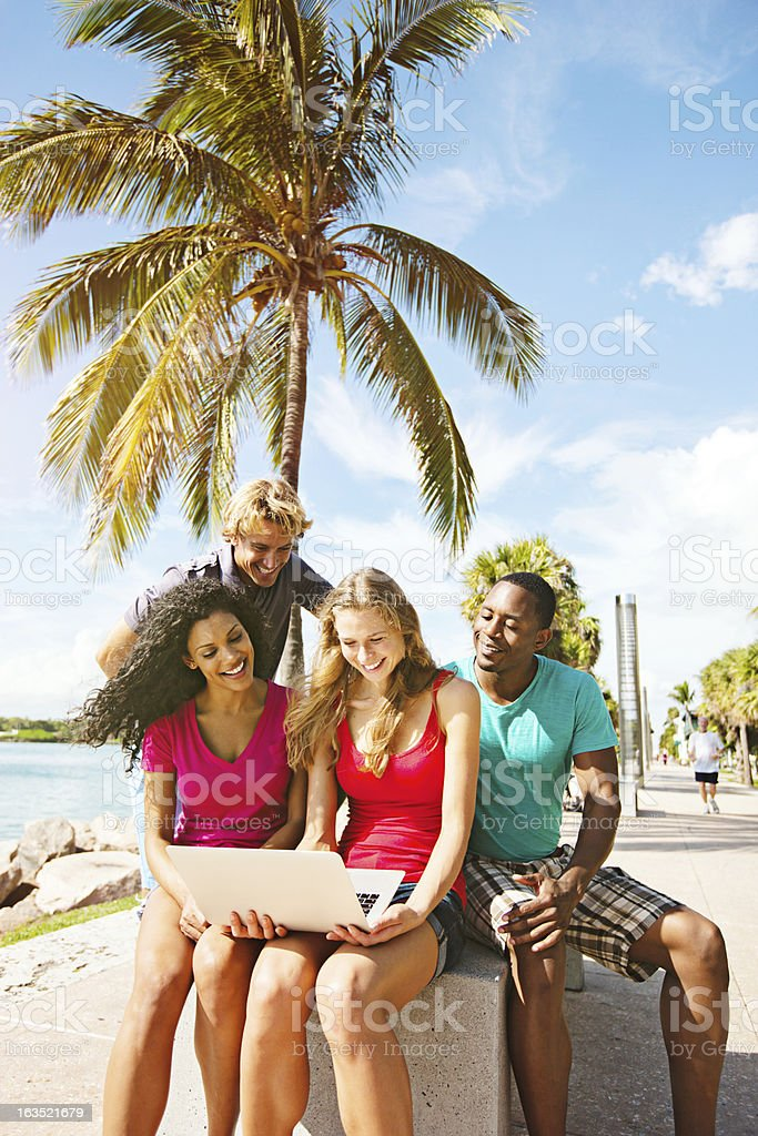 Happy Young Group of Friends Using Laptop Outdoors royalty-free stock photo