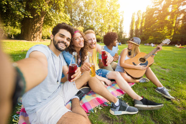 happy young group of people taking a selfie together in park during music festival. - concert selfie stock photos and pictures