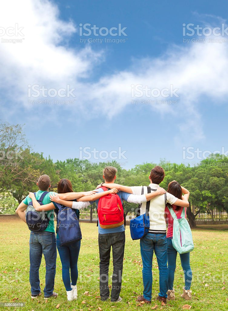 Happy young group of students watching the sky royalty-free stock photo