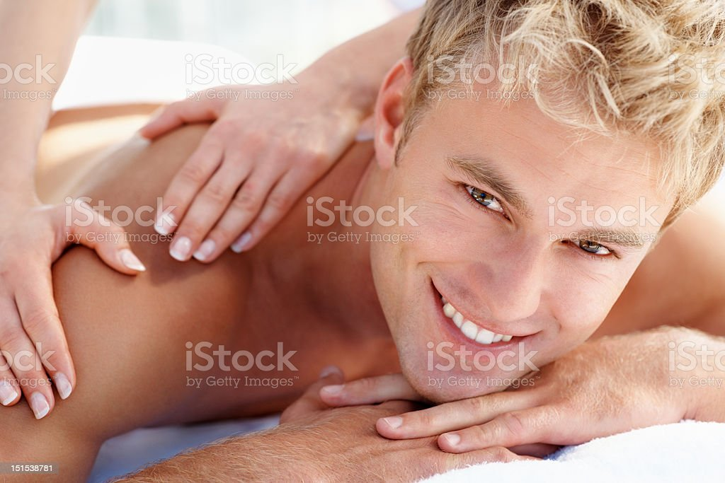 Happy young guy getting shoulder massage at spa royalty-free stock photo