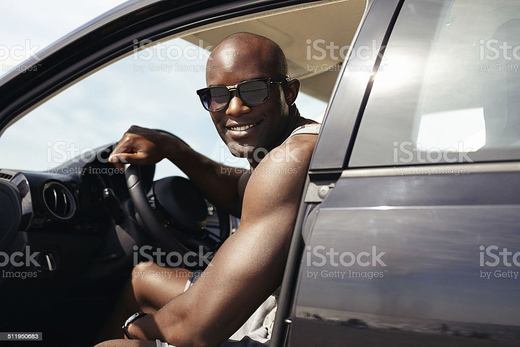 Happy young guy in his car stock photo