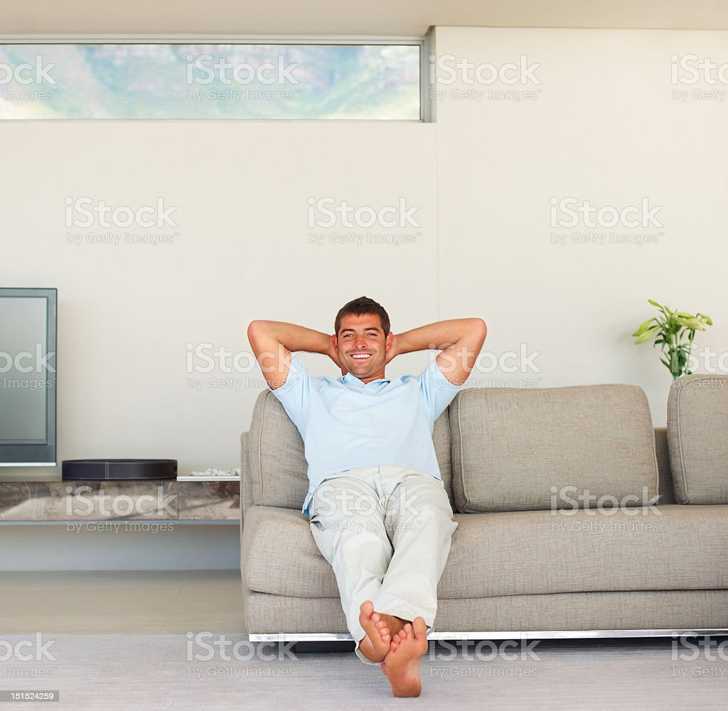 Happy young guy relaxing on couch at home royalty-free stock photo