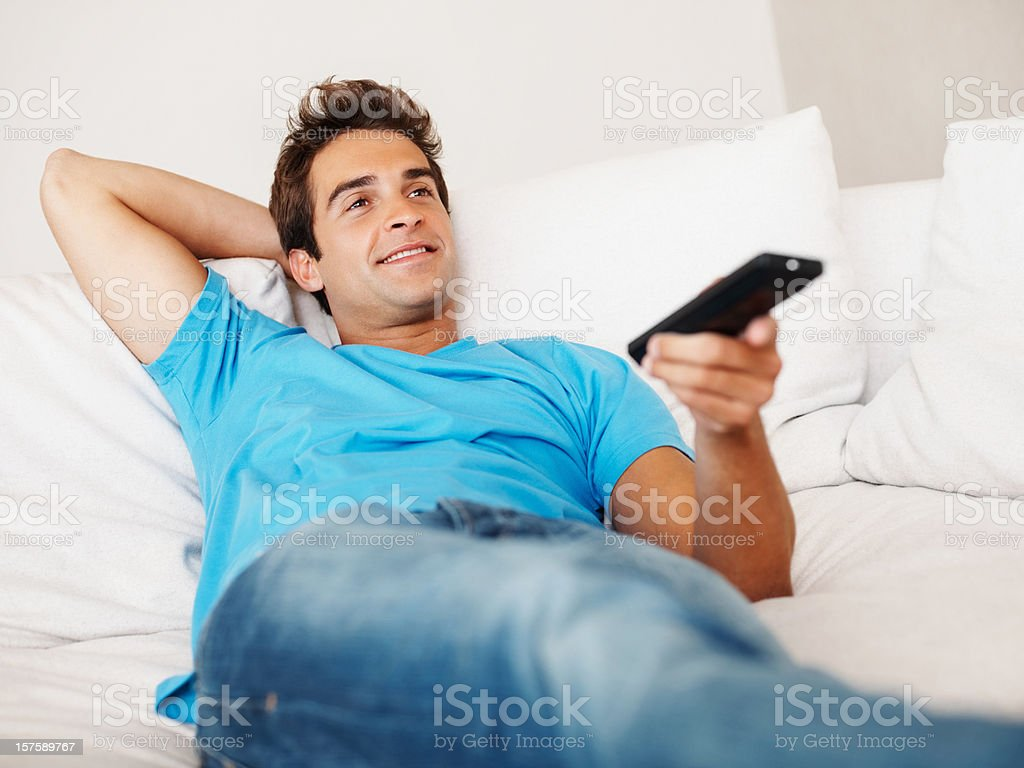 Happy young guy relaxing with remote control in hand royalty-free stock photo