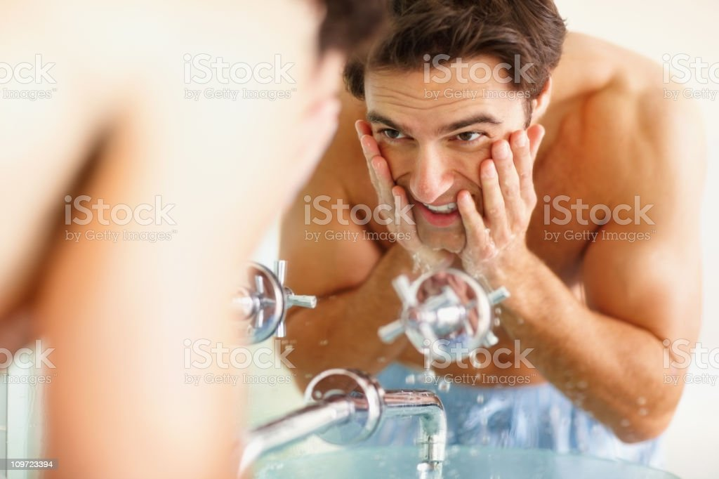 Happy young guy washing his face at the wash basin stock photo