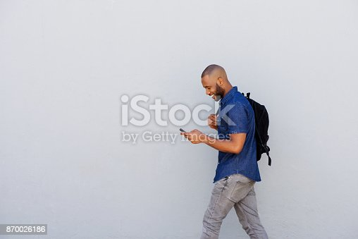 Side portrait of a happy young guy with bag walking outdoors and sending text message by mobile phone