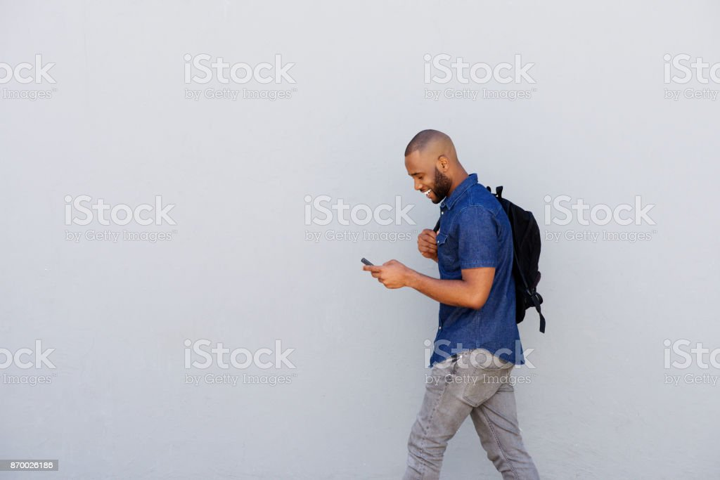 happy young guy with bag walking with mobile phone stock photo