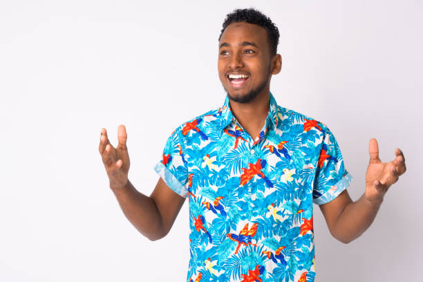 Happy young handsome African tourist man looking surprised stock photo