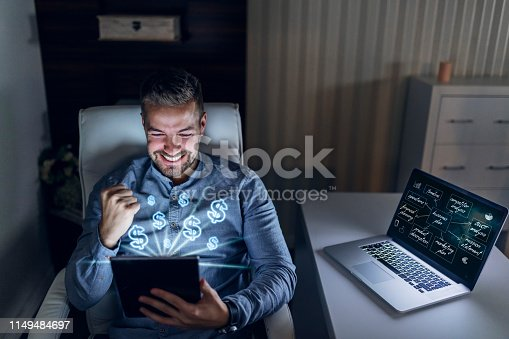 Happy young handsome businessman holding tablet and cheering for earning lots of money. On laptop monitor is business plan.