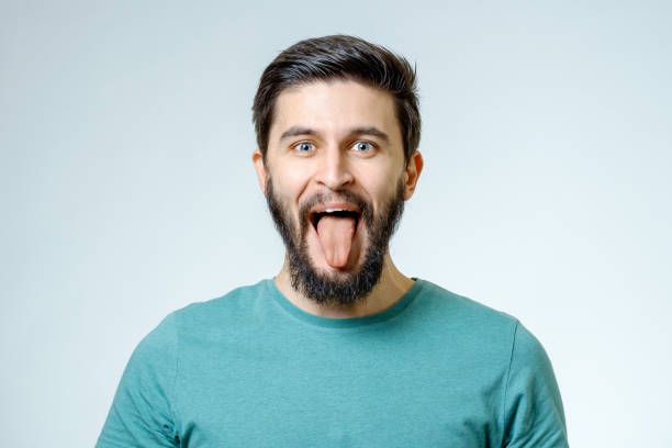 Happy young handsome man gesturing while standing against grey background Happy young handsome man gesturing while standing against grey background sticking out tongue stock pictures, royalty-free photos & images