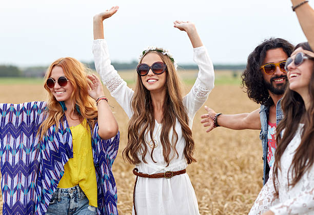 happy young hippie friends dancing on cereal field - hippie fashion stock photos and pictures