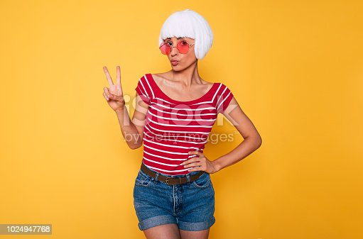 483075616 istock photo Happy young hipster blonde girl in pink sunglasses posing over orange background 1024947768