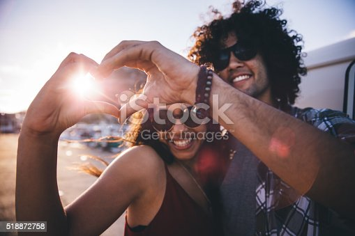 Happy young hipster couple making heart shape with hands close to a vintage van during a summertime road trip
