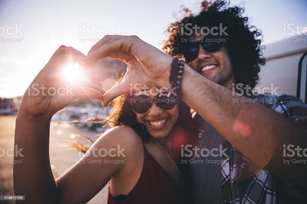 Happy young hipster couple making heart shape with hands stock photo