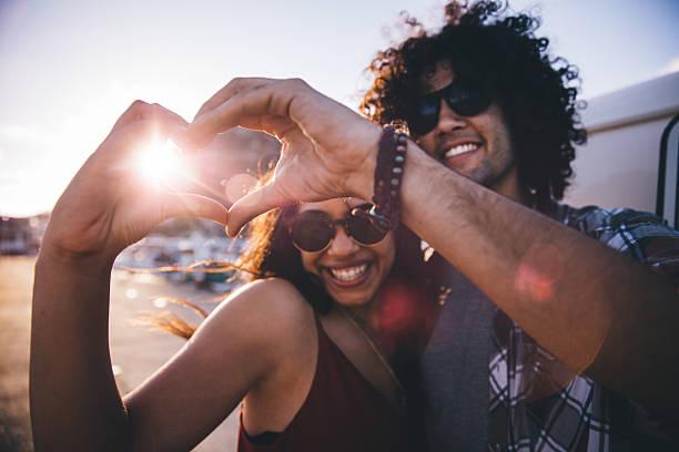 felice giovane coppia hipster facendo un cuore forma con le mani - spiaggia coppia amore foto e immagini stock