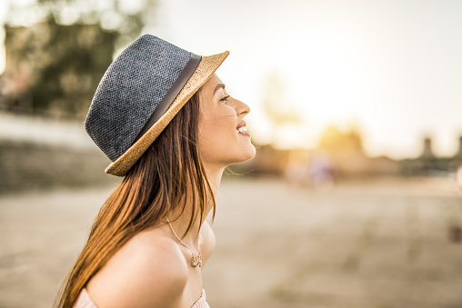 Happy young hipster woman day dreaming on a beautiful sunset in the city.