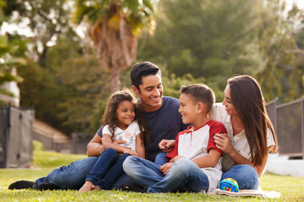 Happy young Hispanic family sitting together on the grass in the park, looking at each other Happy young Hispanic family sitting together on the grass in the park, looking at each other latin american and hispanic ethnicity stock pictures, royalty-free photos & images