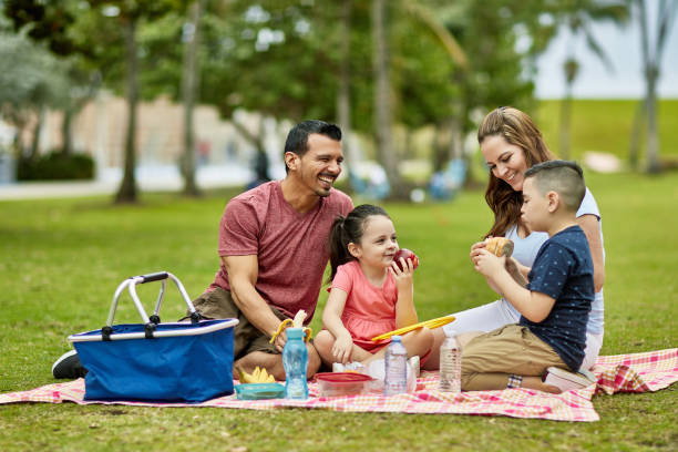 Happy Young Hispanic Family Spending Time Together at Park stock photo