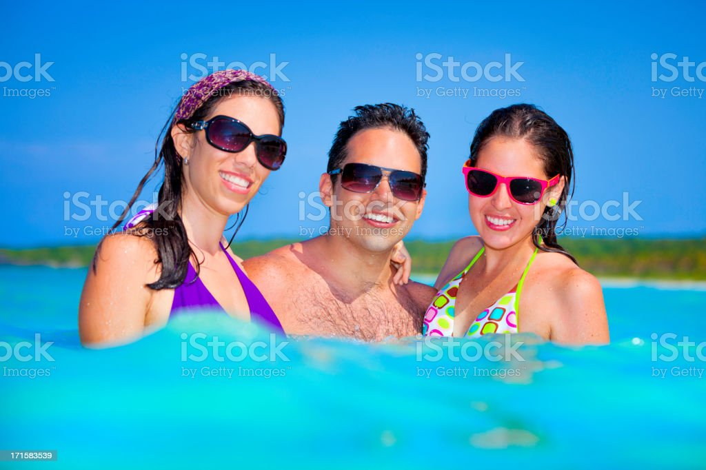 Happy young hispanic friends in a turquoise tropical beach royalty-free stock photo