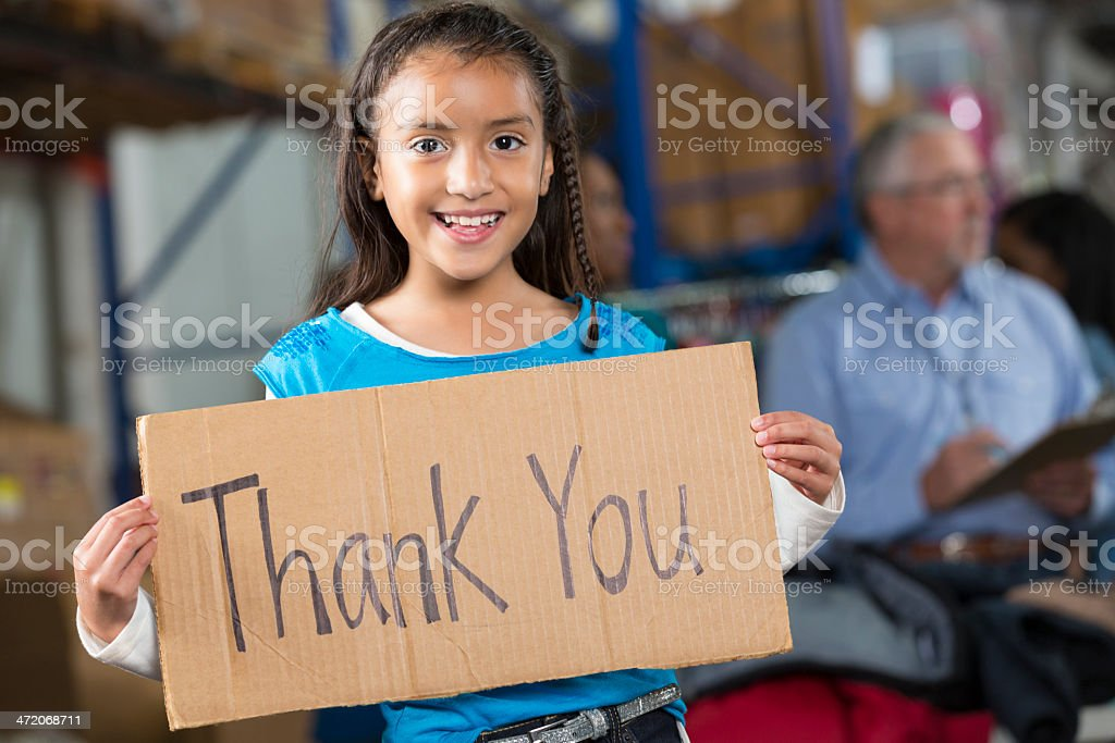 Happy young Hispanic girl holding Thank You sign in warehouse stock photo