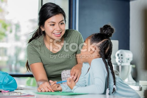 Young adult Hispanic woman is smiling while babysitting and tutoring African American little girl. Nanny is assisting child with her homework in modern kitchen.