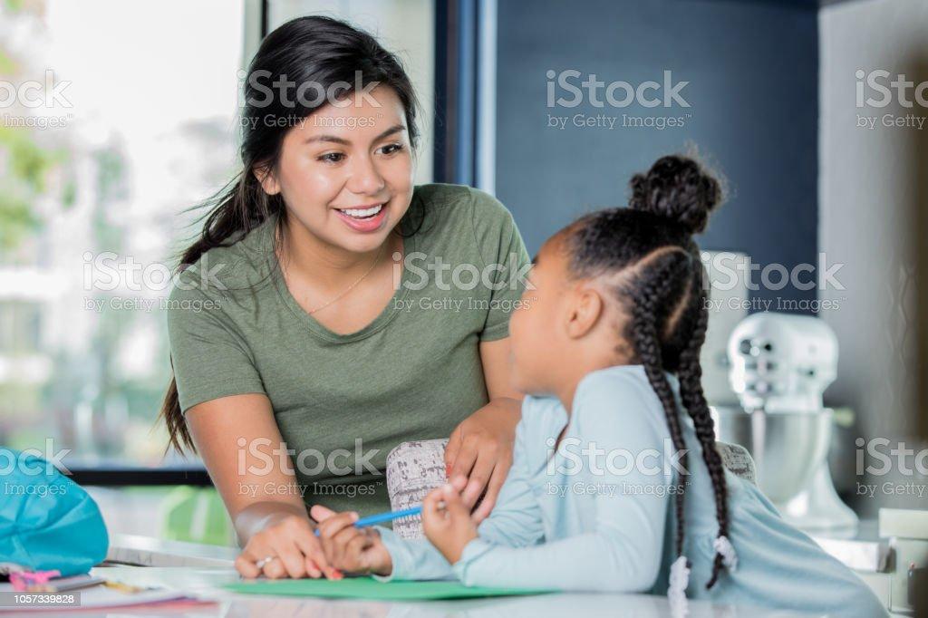 Happy young Hispanic woman is babysitting, tutoring elementary age girl. stock photo