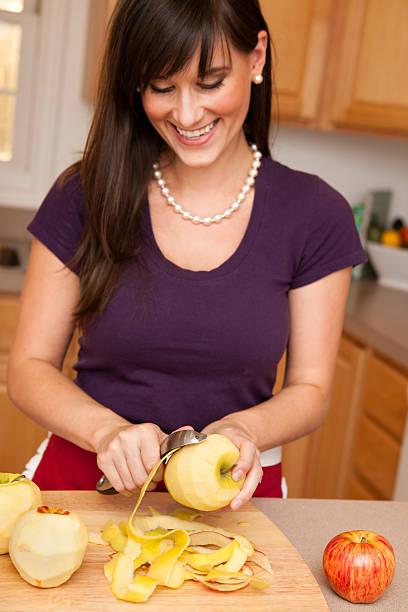 glückliche junge hausfrau peeling äpfel in der küche - peeling zu hause machen stock-fotos und bilder