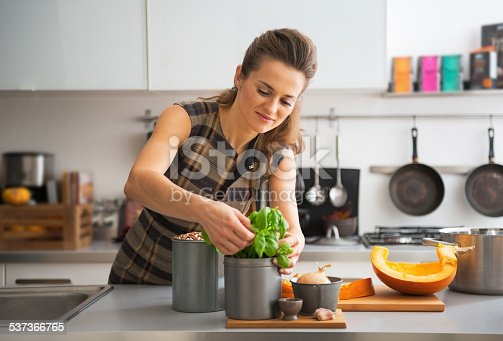 istock happy young housewife using fresh basil while cooking in kitchen 537366765
