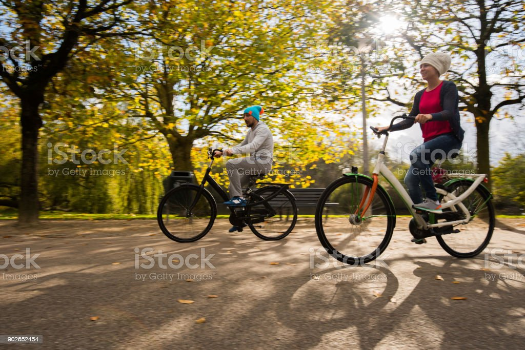 Happy Young In Love Couple Riding Bikes In Nature At Sunny Autumn