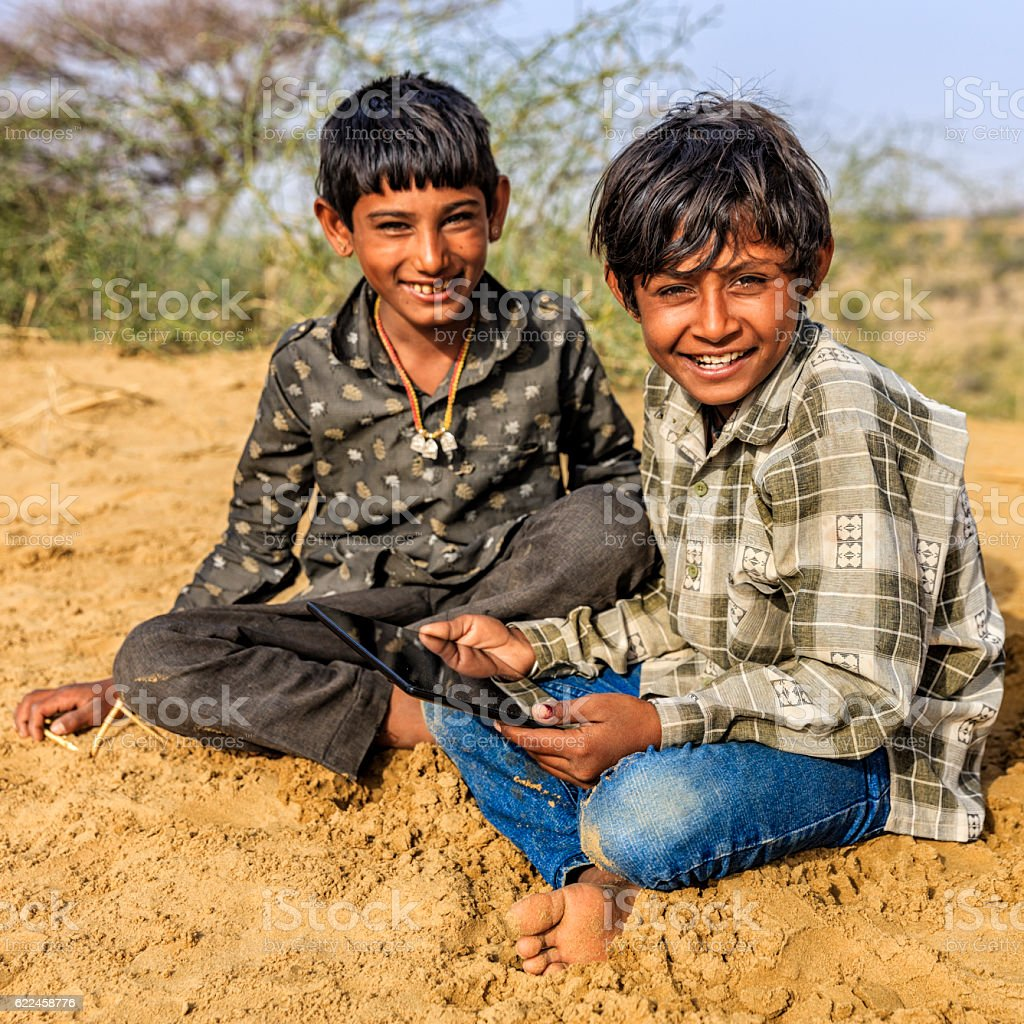 Happy young Indian boys using digital tablet, desert village, India royalty-free stock photo