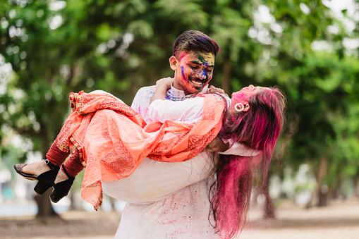 Happy Young Indian couples celebrating Holi festival