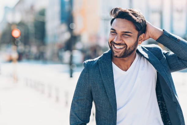 Happy young Indian ethnicity man on the street Happy young man walking outdoors in the city hand in hair stock pictures, royalty-free photos & images