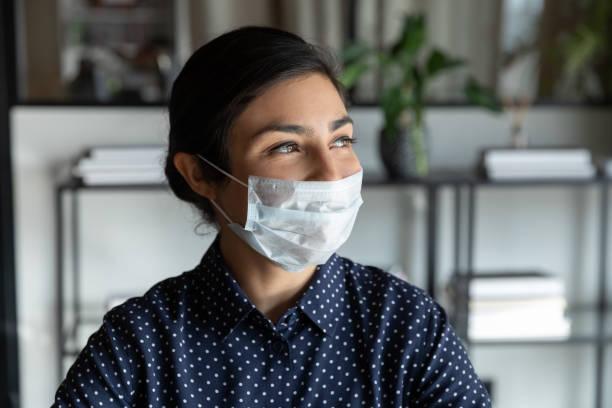 Glückliche junge indische Managerin in Schutzmaske, die wegschaut. – Foto