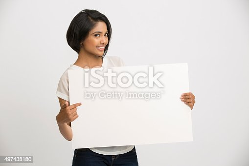 istock Happy young Indian woman holding a blank billboard 497438180