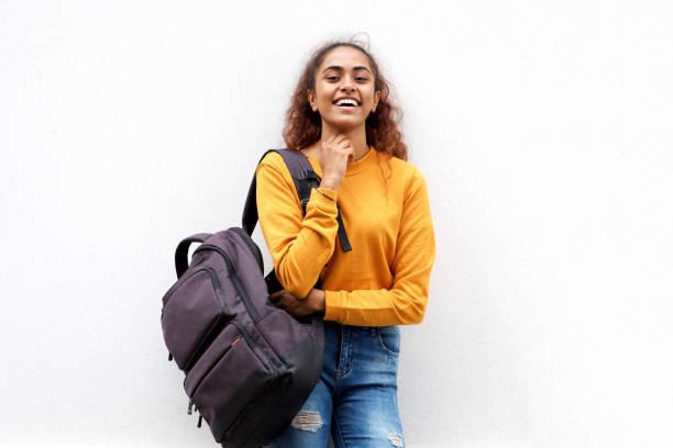 glückliche junge indische Frau lacht mit Rucksacktasche vor weißem Hintergrund – Foto
