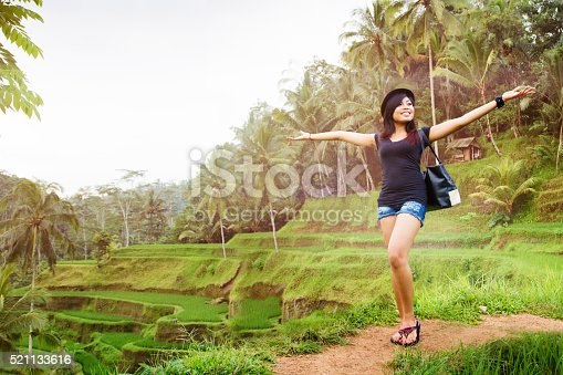 Happy young Indonesian woman proudly shows off Bali landscape at a terraced rice paddy.