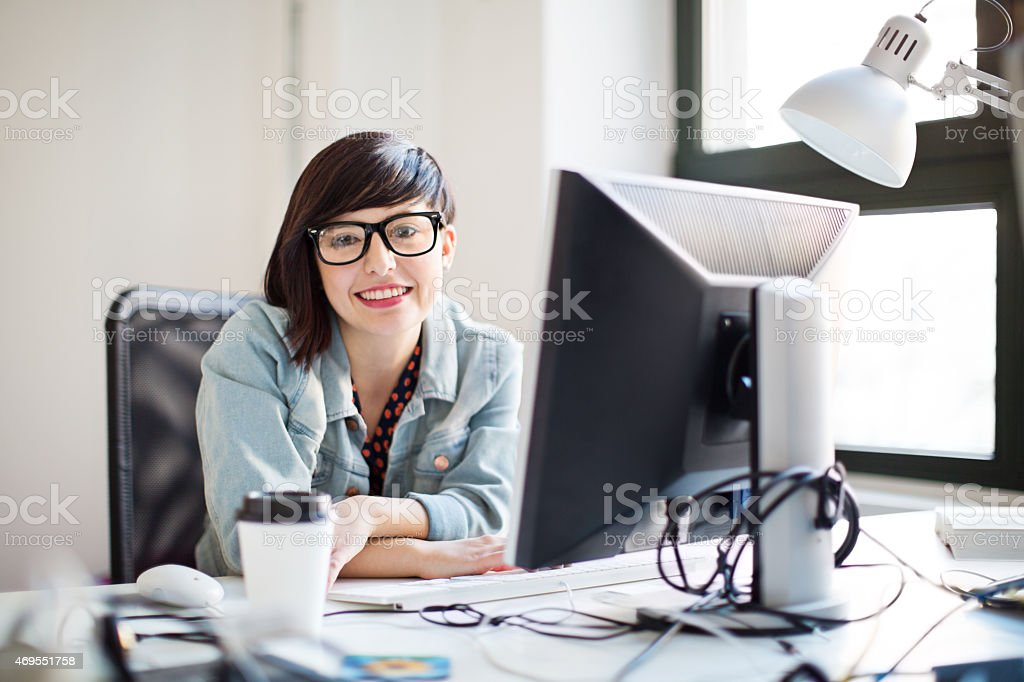 Happy young IT professional at her desk stock photo