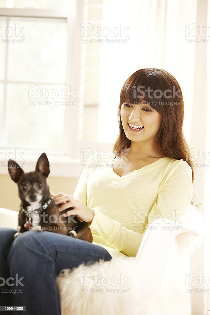 Happy young Japanese woman with her pet dog on sofa royalty-free stock photo