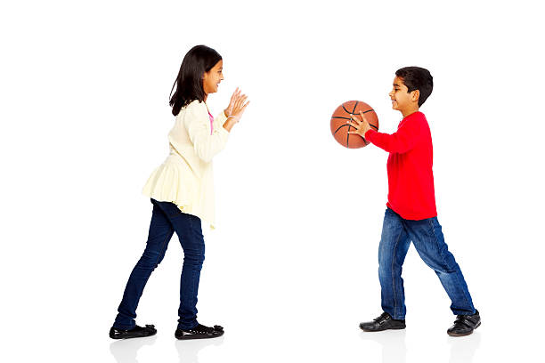 Happy young kids playing basketball stock photo